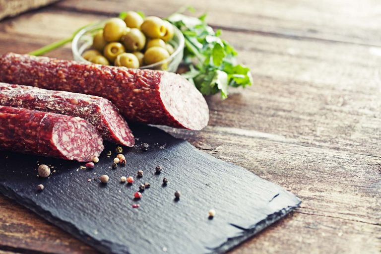 fresh salami laid out on a stone board